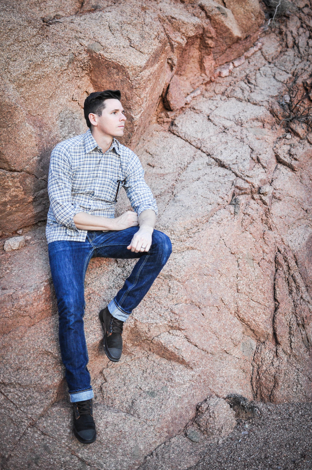 Man in jeans sitting on rocks