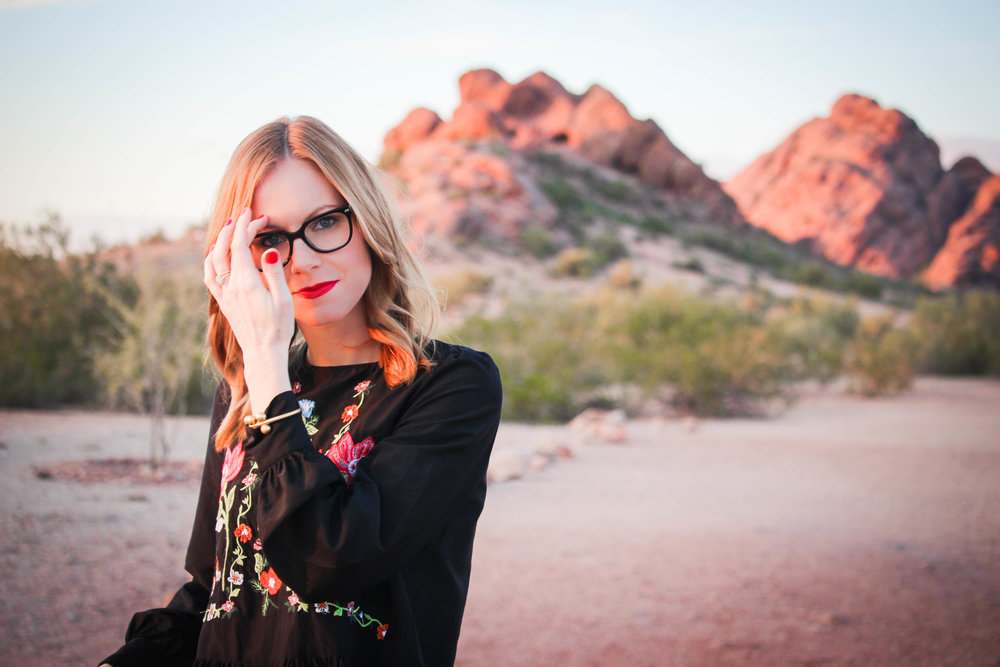 woman in glasses and black top in desert