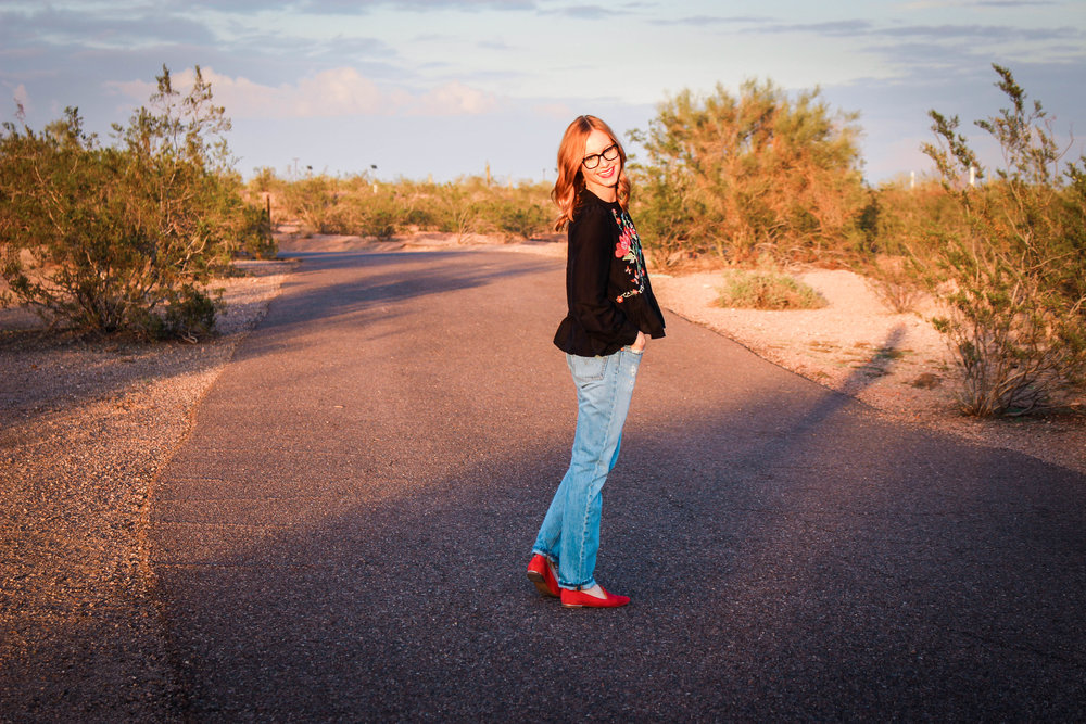 woman in black top and jeans in desert