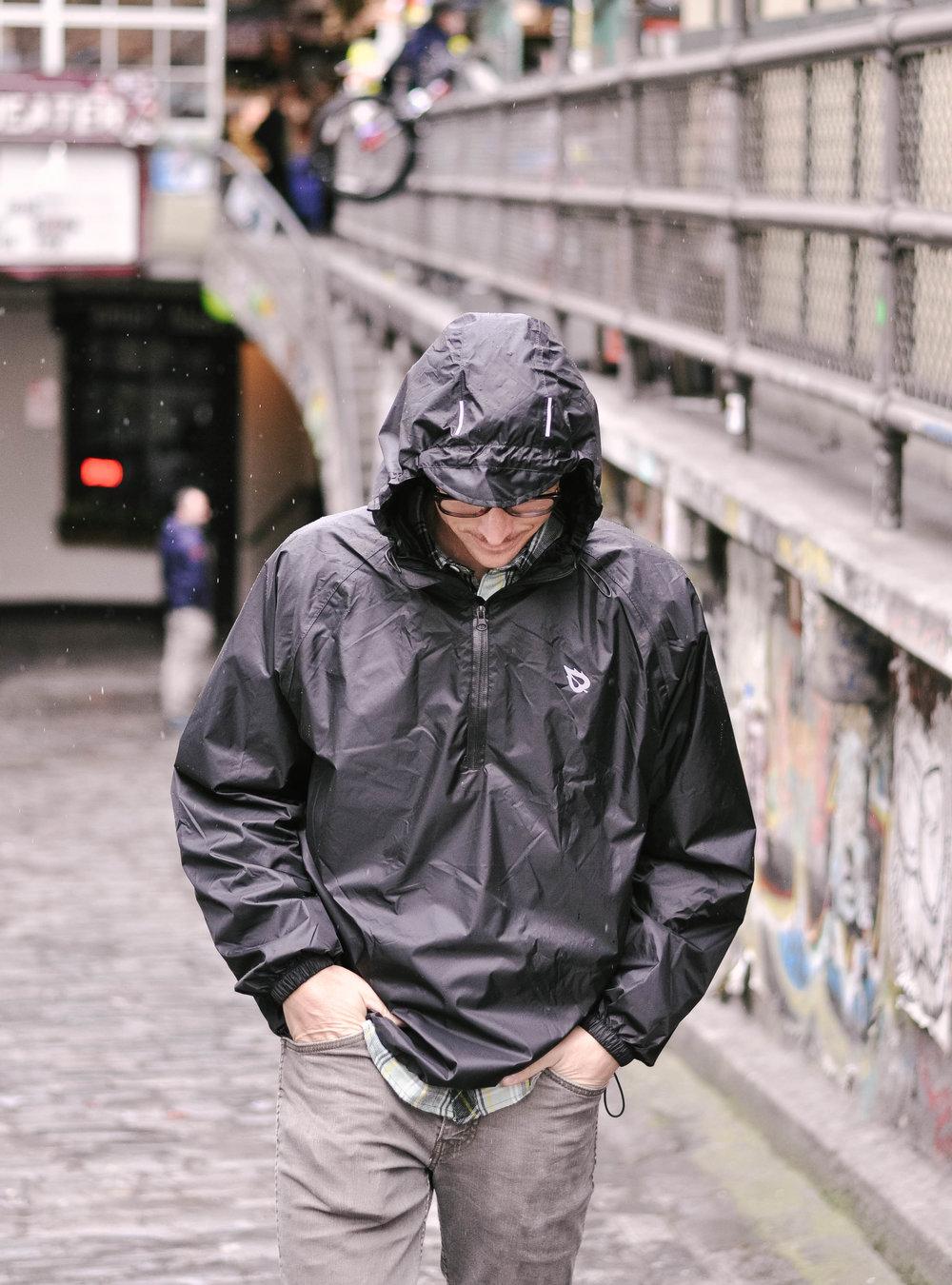 Man wearing raincoat walking in rain