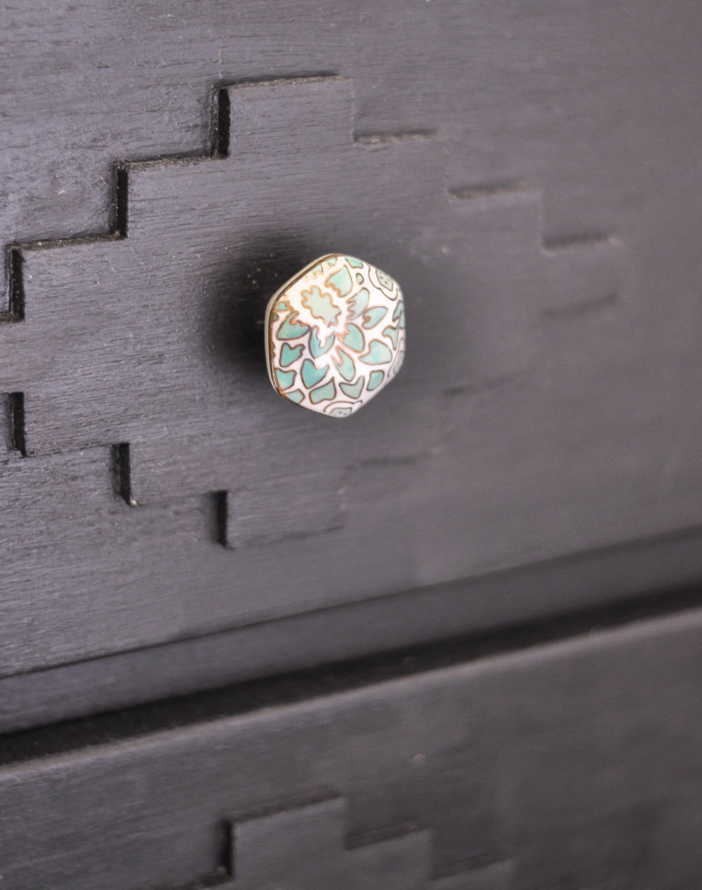 anthropologie decorative knob on black wooden dresser