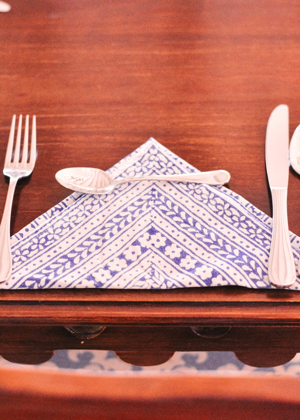 Place setting with blue and white napkin on wooden table