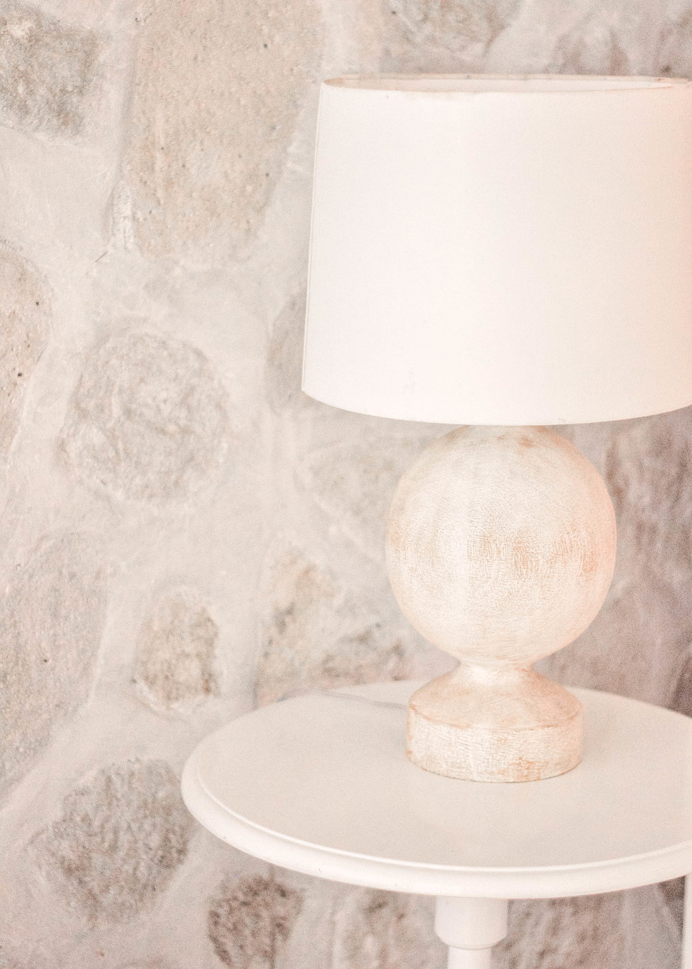 White lamp against stone wall