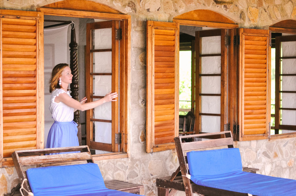woman opening wooden shutters