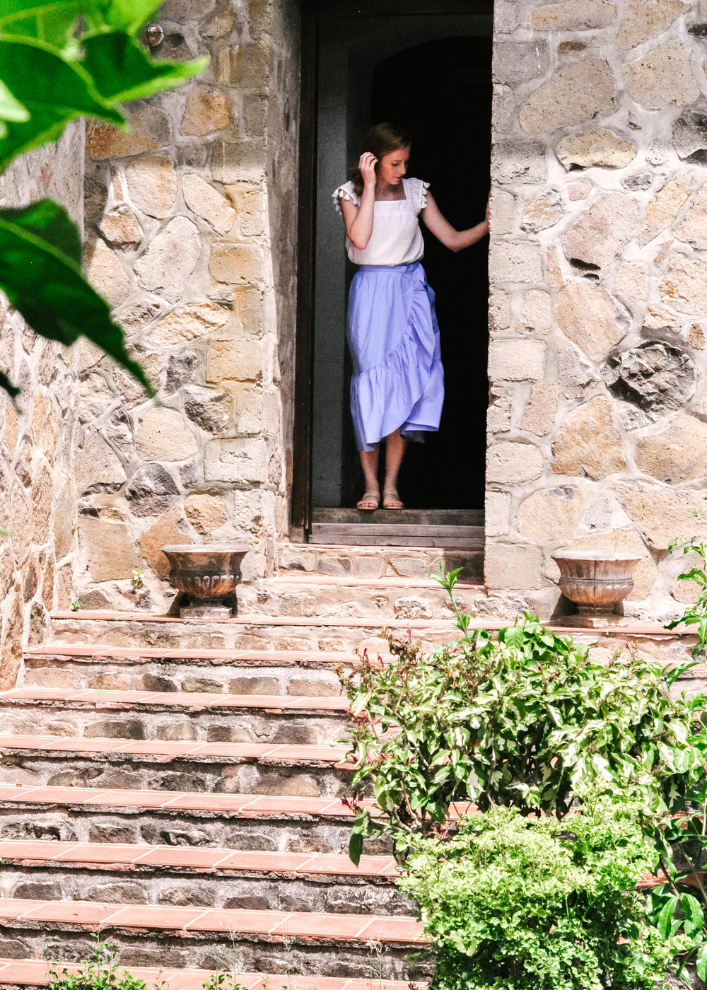 Woman walking out of stone house