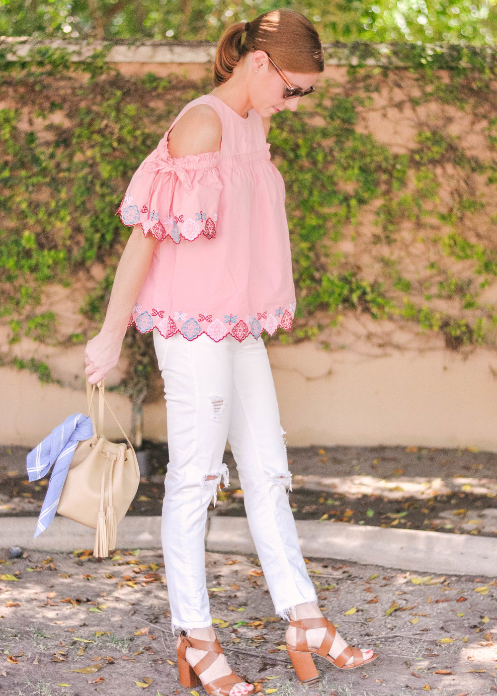 woman in pink Loft top with white Zara jeans and tan J.Crew handbag