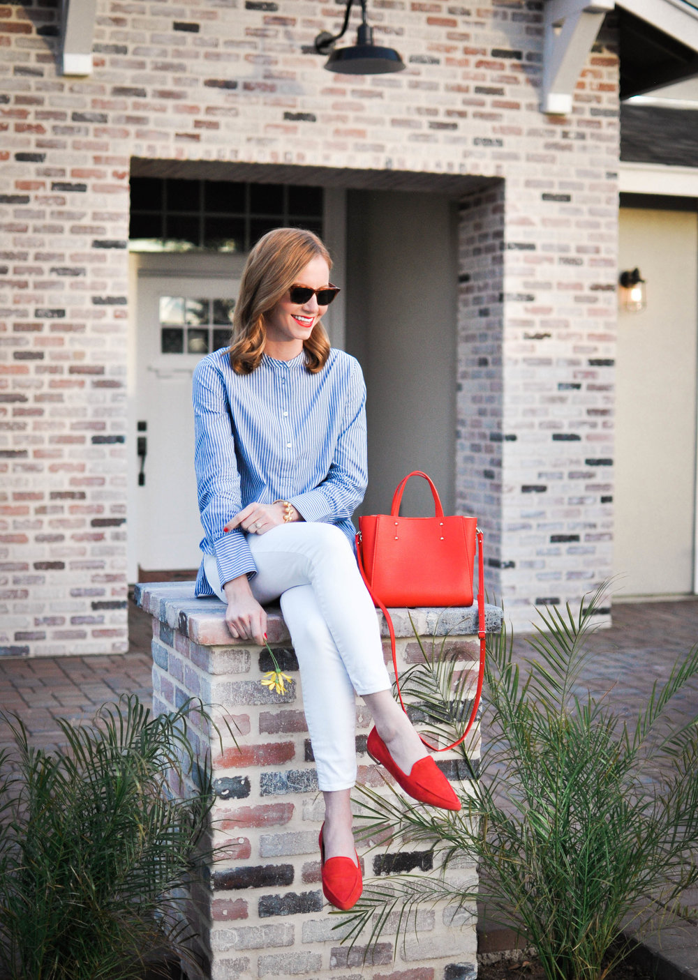 woman in chambray top with red purse