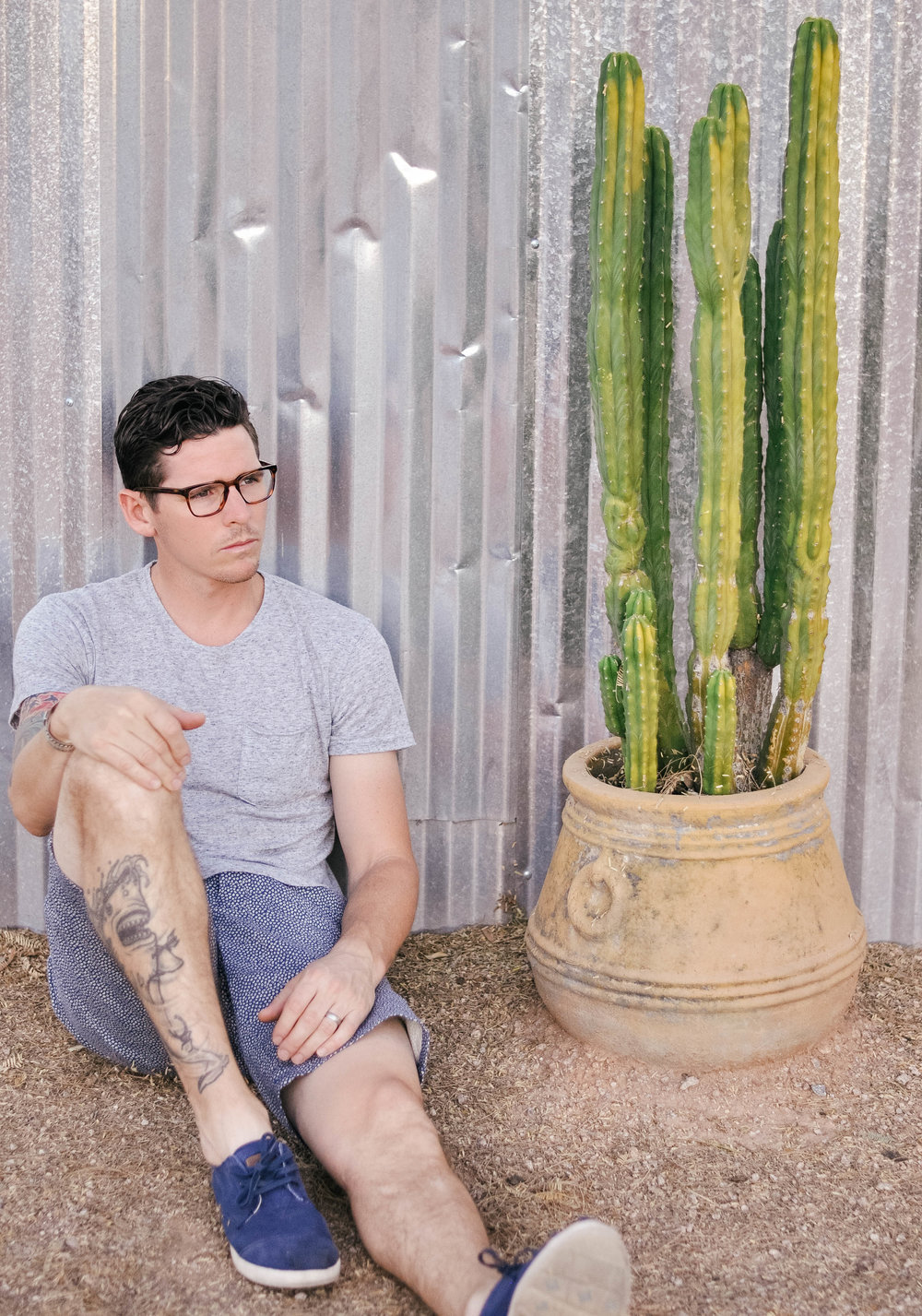 man in glasses sitting on ground next to cactus