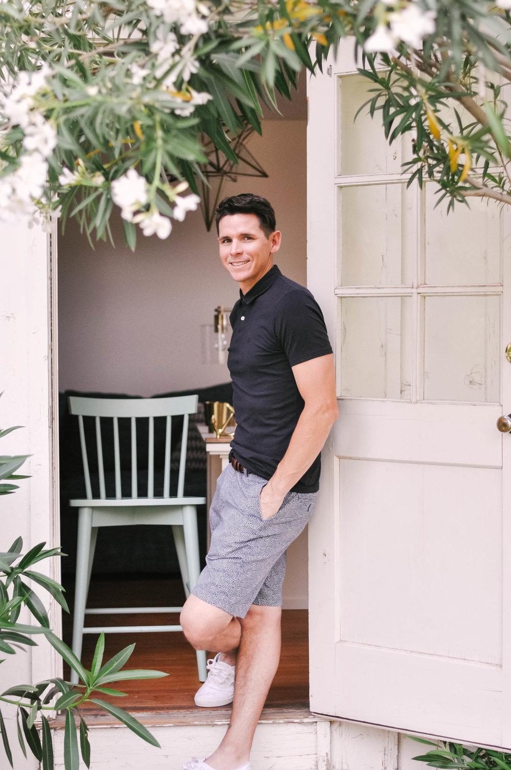 man in shorts posing against door frame