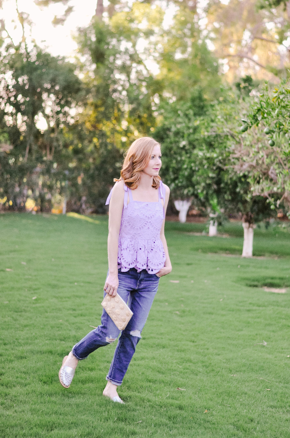Woman walking in purple eyelet tie shoulder top with jeans and huaraches