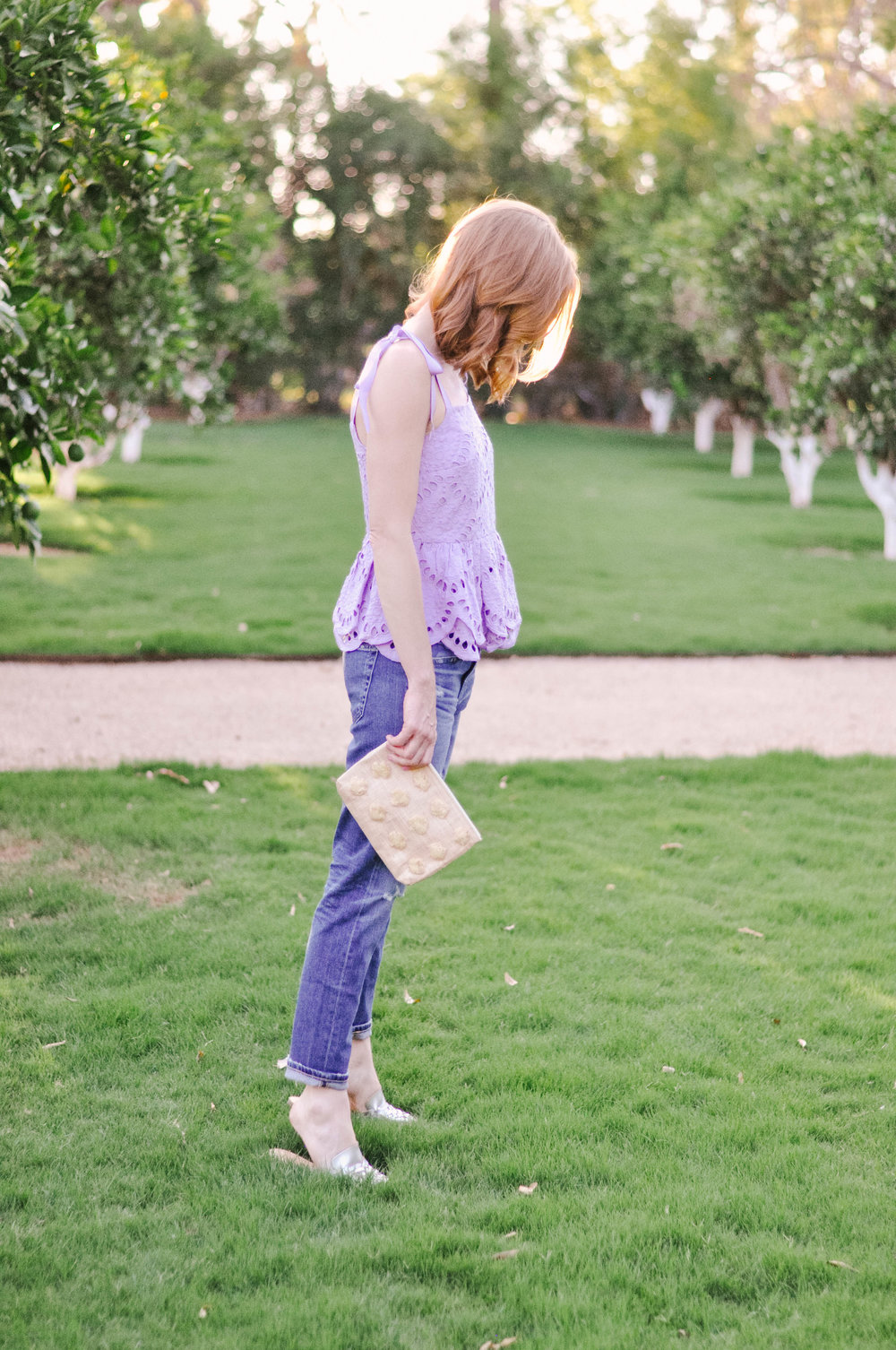 woman with red hair looking at grass in a lavender eyelet top boyfriend jeans and silver huaraches