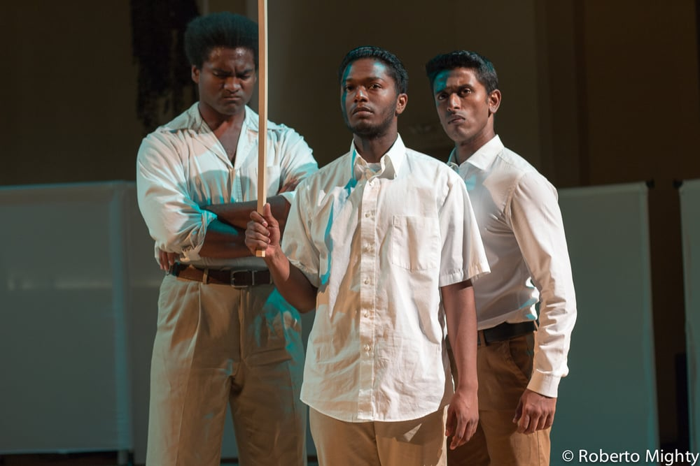 Twelve actors play more than 90 roles between them in The Draft. The student protesters in this scene are portrayed (from left) by Stewart Evan Smith, Trinidad Ramkissoon, and Jacob Athyal. (Photo Credit: Roberto Mighty).