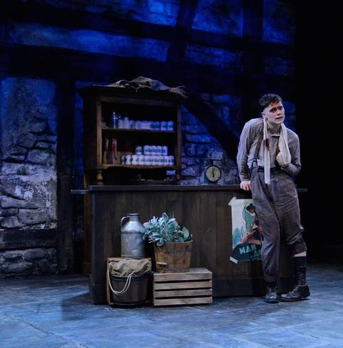 Billy Claven (Conor Proft, BU CFA '16) leans against the counter of the dry goods store in Inishmaan in Boston University College of Fine Arts'  The Cripple of Inishmaan  (Photo Credit:  Kal Zabarsky ).