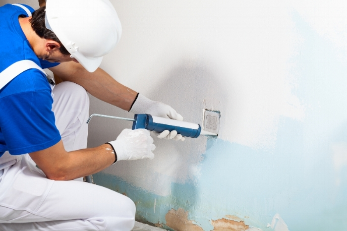 Close-up Of Professional Workman Applying Silicone Sealant With Caulking Gun On To A Wall