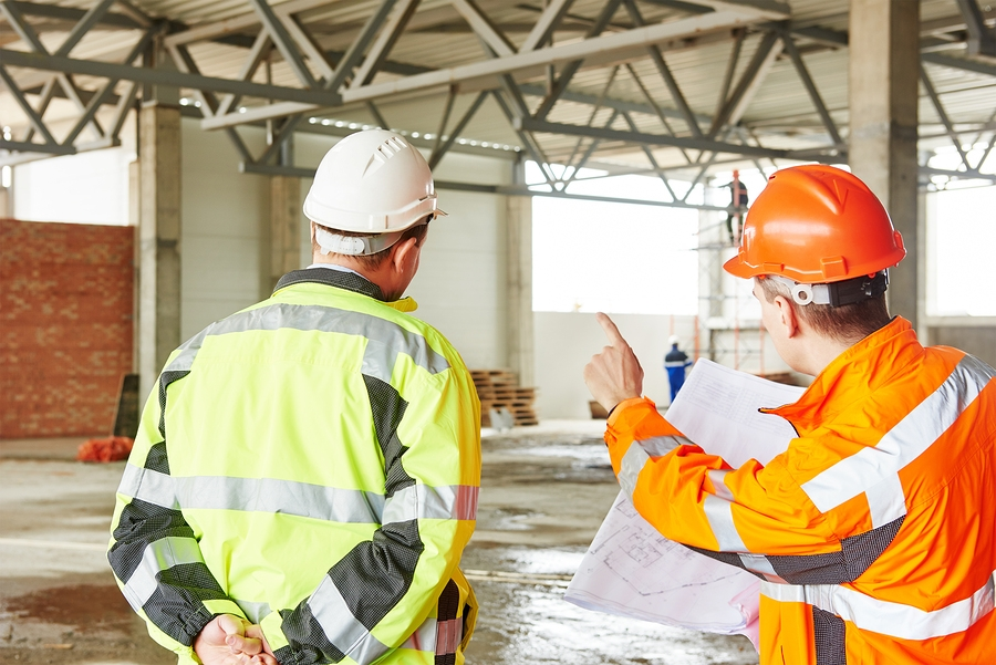 Photo engineers construction foreman managers outdoors at building site with blueprints.jpg