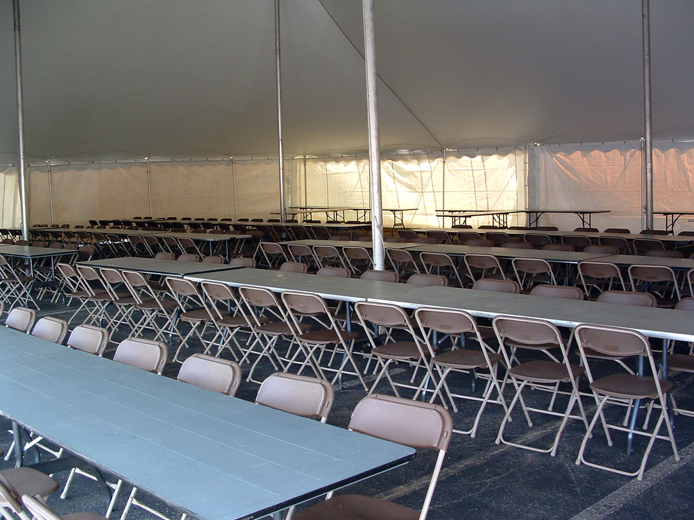 Brown folding chairs and 8' banquet tables