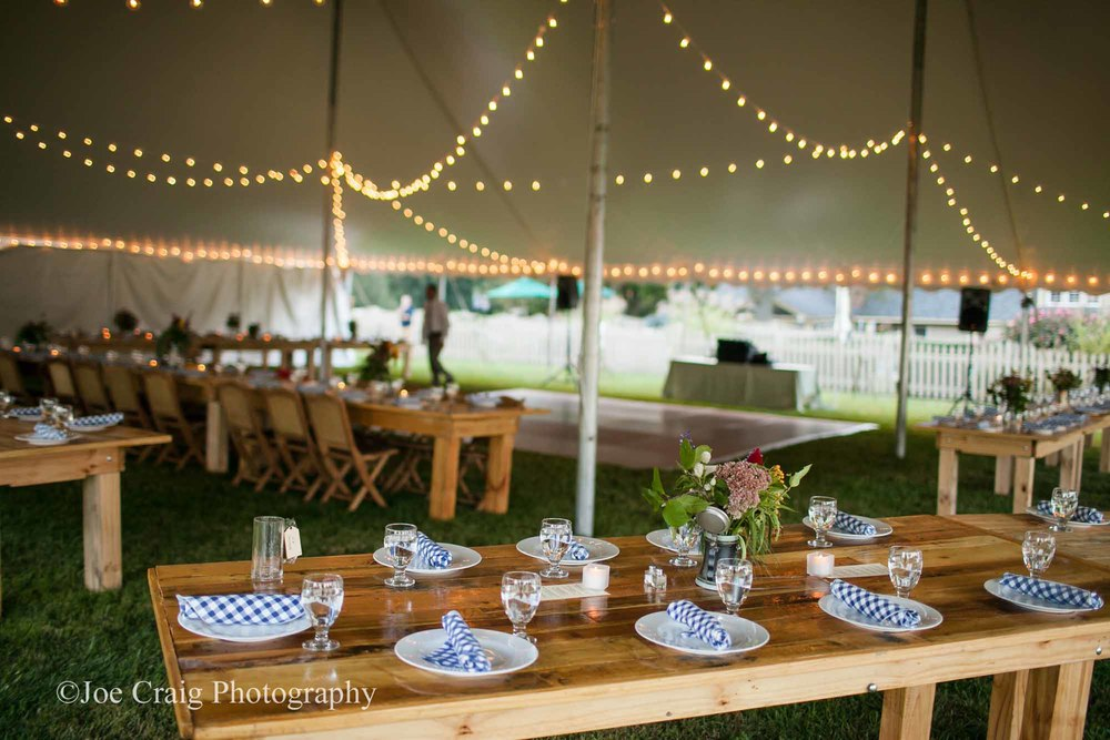 Wedding tent with farm tables and cafe lights