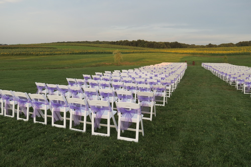 White padded chairs with purple sashes