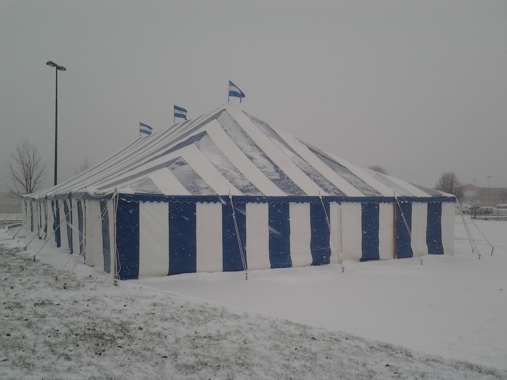 Blue and white striped tent in a snow storm
