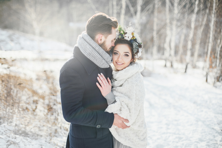 The bride and groom hugging. Beautiful couple walking in the Park in winter.
