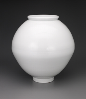 """PHOTO: SUSAN COLE   MOON JAR  2007  PARK YOUNG-SOOK  KOREAN, BORN 1947  Park Young-sook, who has owned and operated her own kiln since 1982, is renowned for her re-creation of the white porcelain wares, or paekcha, once used by the royal Joseon court. This """"full moon"""" jar, with a milky white body and an all-over transparent glaze, unites the purity of form of traditional Korean pottery with modern technical prowess. Park experimented for several years with the form until she was satisfied with the integrity of the finished piece and its contemporary relevance. Porcelain with clear glaze, 20 x 19 1/2in. (50.8 x 49.5cm), Gift of Frank S. Bayley III, in honor of the 75th Anniversary of the Seattle Art Museum, 2007.86, © Young Sook Park   Signed: Signed on bottom of jar   Inscribed: Inscription by cobalt blue """"Mae Hyung, May 7th, 2007"""" at the bottom of the jar.   Provenance: Donor purchased from the artist  Currently Not On View."""