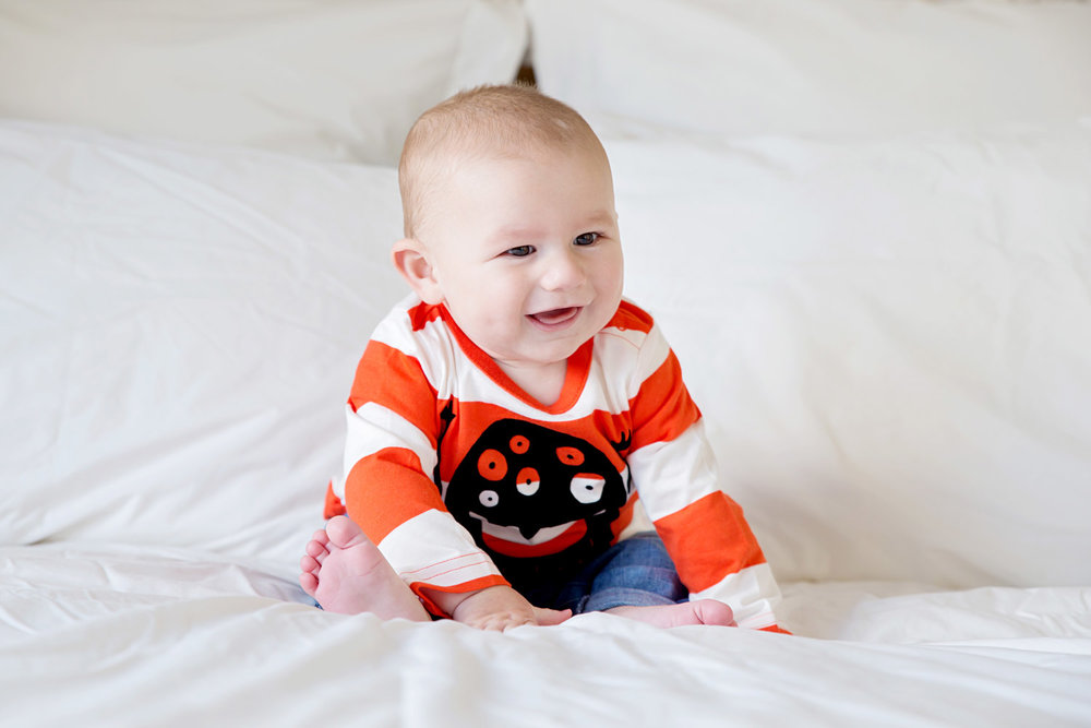 Baby pictures - 8 month old Harry on a big bed in a Halloween t-shirt