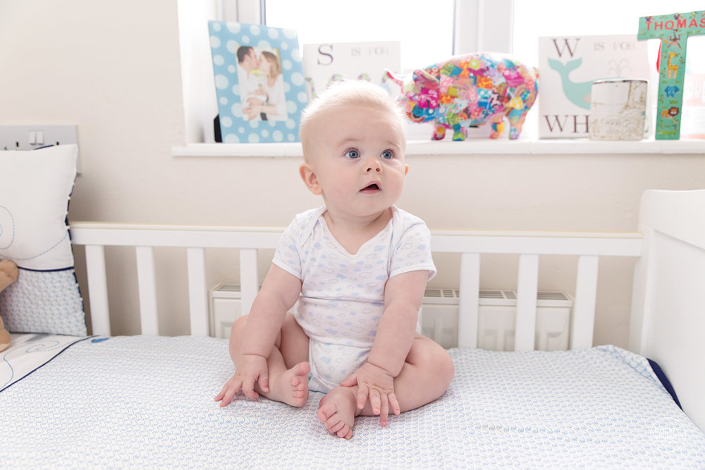 BABY PICTURES - 6 month old happily sits in his cot