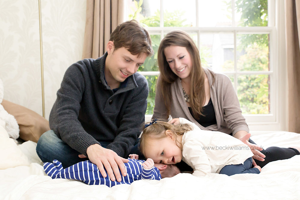 Family photography with newborn on bed, St Albans