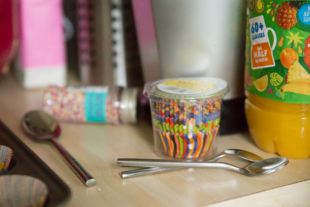 Colourful cake sprinkles, cup cake cases and spoons.