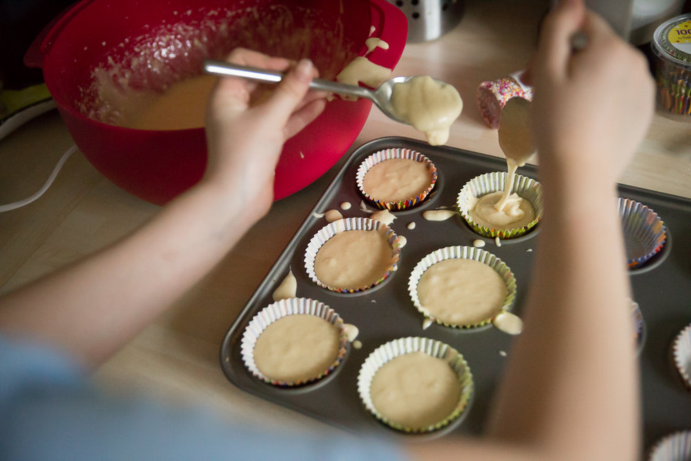 Image of girl putting cake mixture into colour cup cake cases.