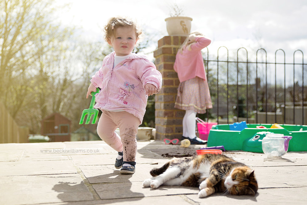muddy 1 year old holds green fork with her cat in the garden