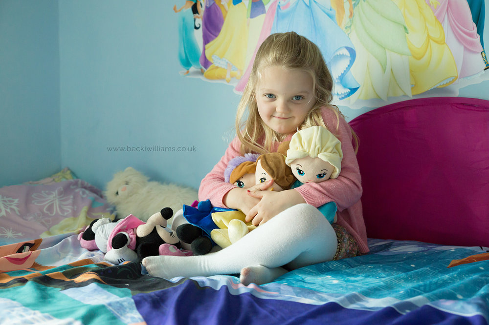 big sister hugs disney dolls for family photo shoot