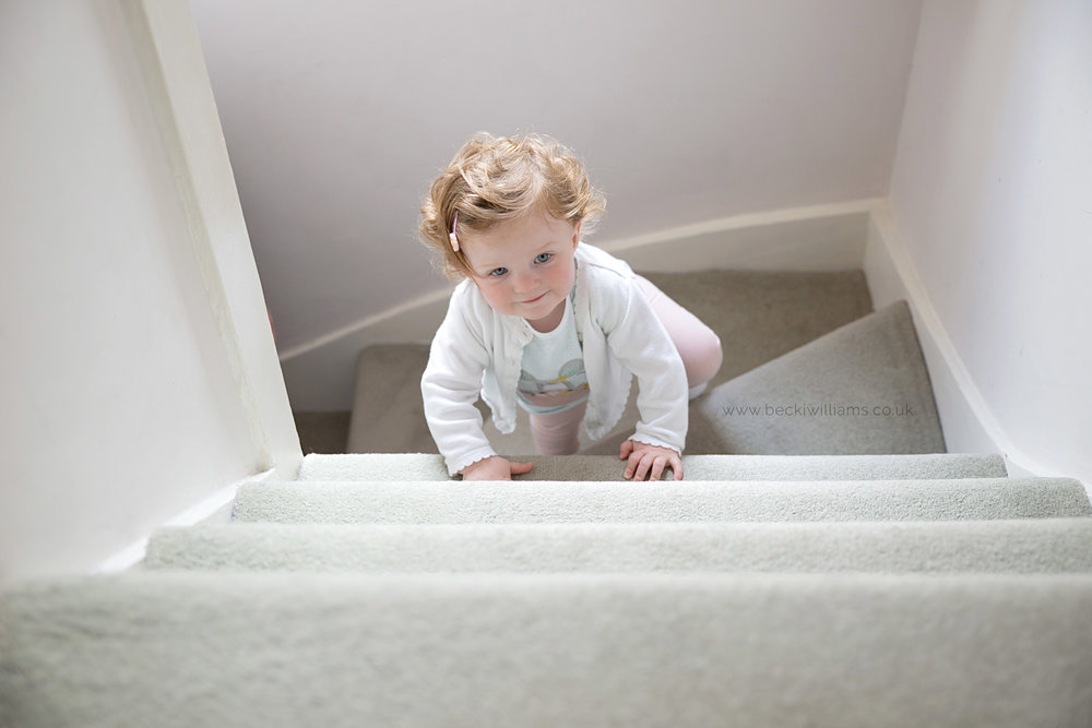 1 year old climbs stairs in baby photo shoot
