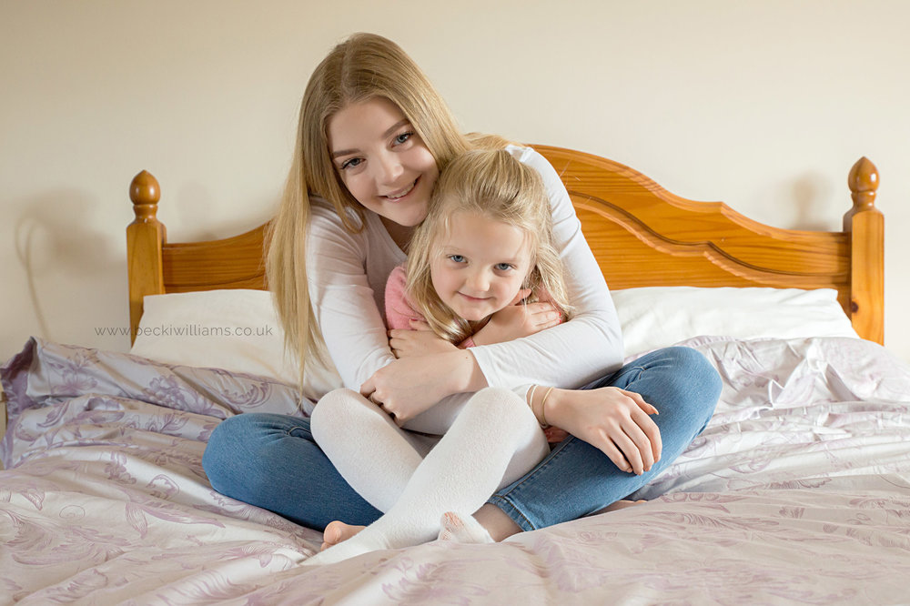 sisterly cuddles on a bed for family photo shoot