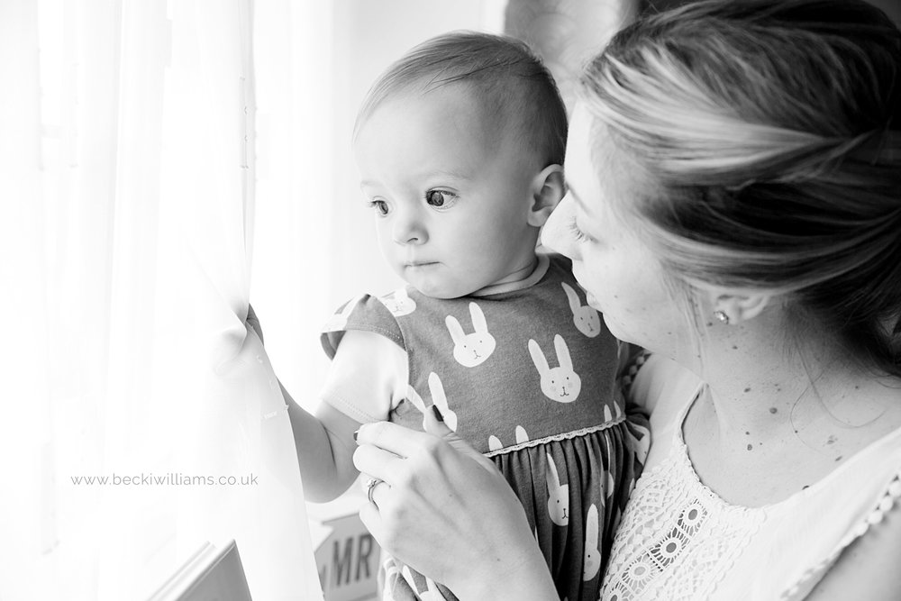 1 year old looking out the window with her mum