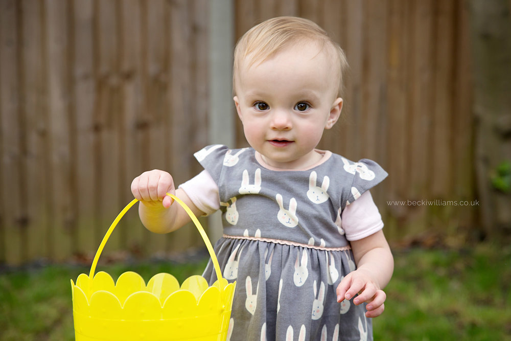 1 year old holding easter basket for photography shoot in luton