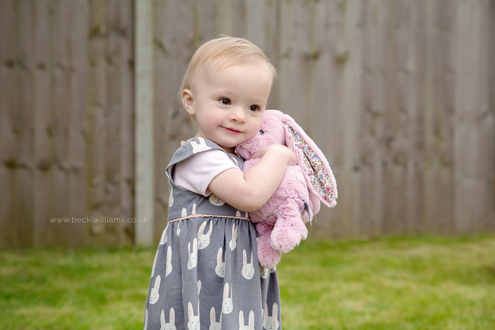 1 year old cuddles pink bunny in the garden.  hemel hempstead photography