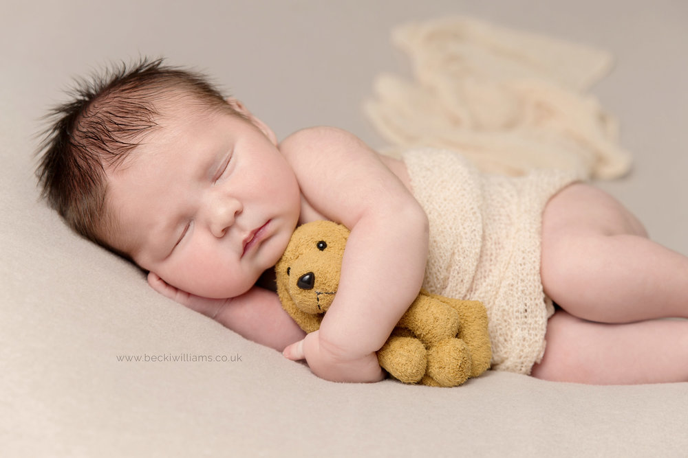 Newborn pictures in hemel hempstead - asleep baby in cream wrap with toy dog