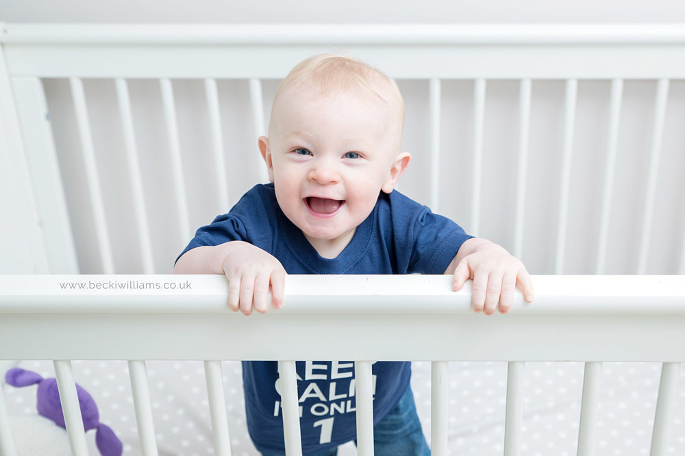 1 year old boy in white cot for professional photo shoot