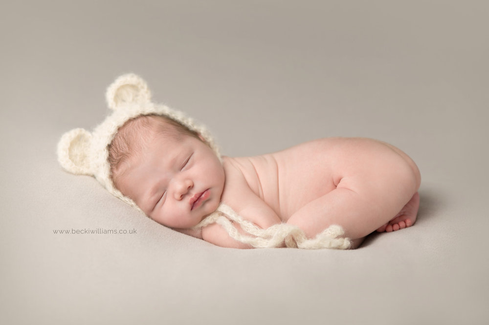 professional photo shoot of newborn baby in hemel hempstead.  baby laying on it's tummy wearing a cute bear hat.