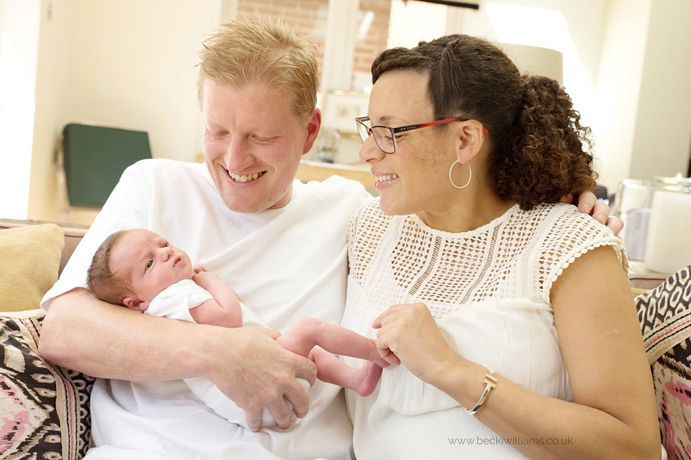 family cuddles newborn during professional photography in hitchin