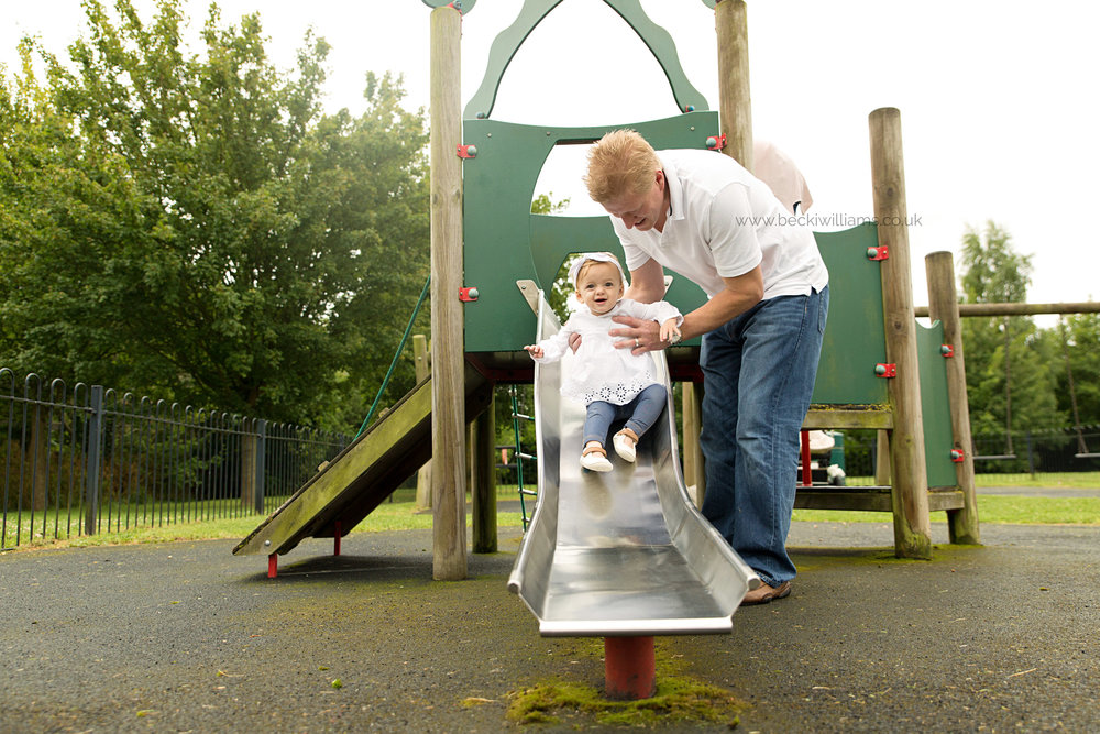 1 year old on a slide with her dad in the park for professional photography