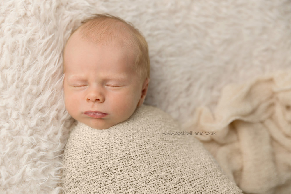 newborn boy wrapped in a cream wrap on a fur rug for his newborn photo shoot