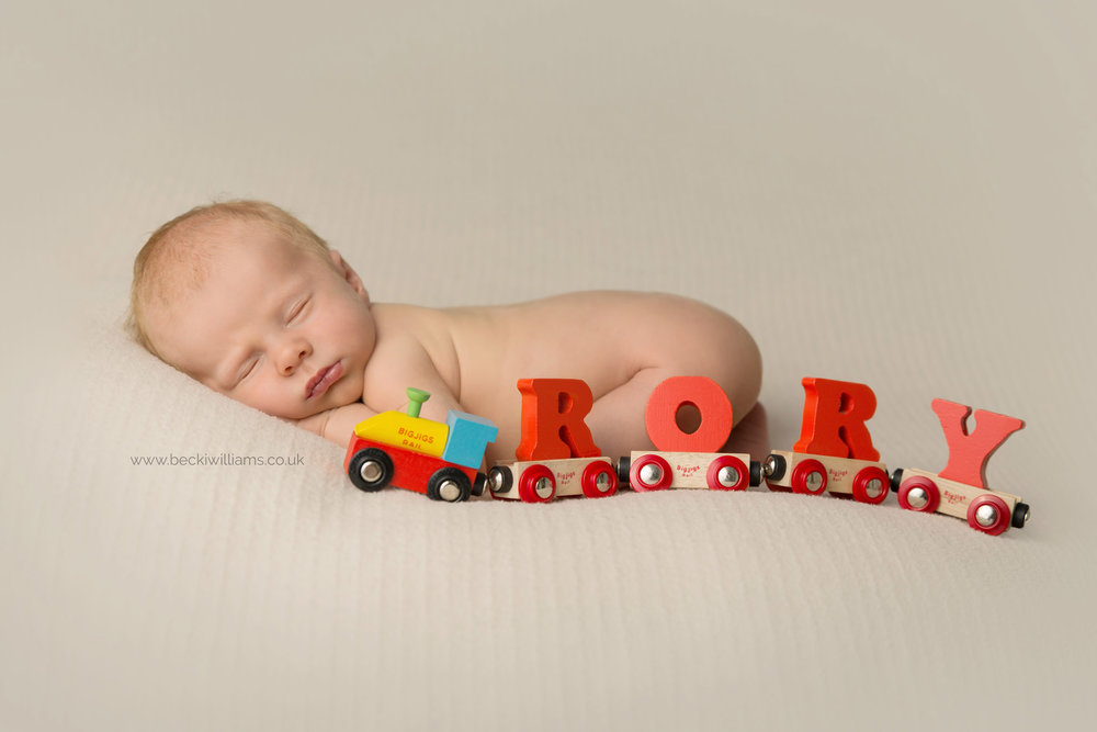 newborn boy asleep on his tummy with a red train spelling out his name