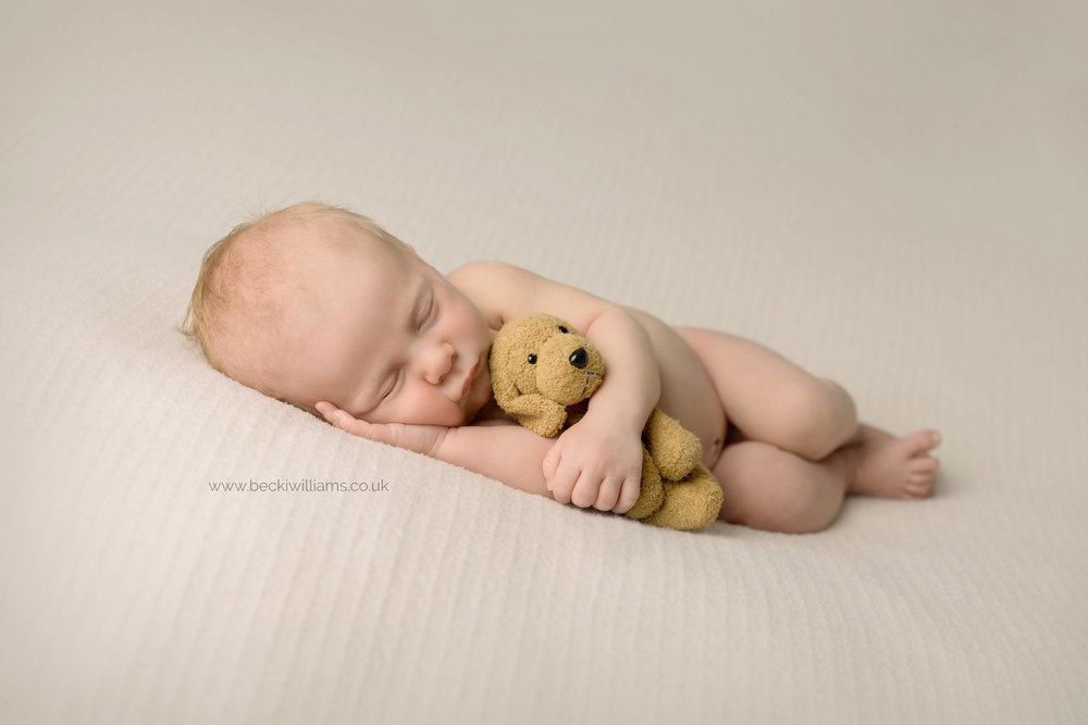 newborn boy cuddles toy dog while asleep