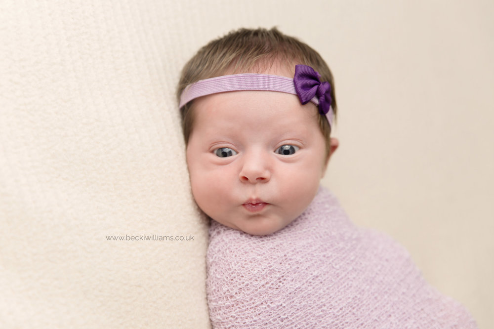 Newborn pulls funny face during her newborn baby photo shoot in Hemel Hempstead