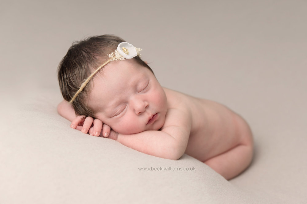 Newborn baby girl wears white headband during her baby photo shoot in Hemel Hempstead