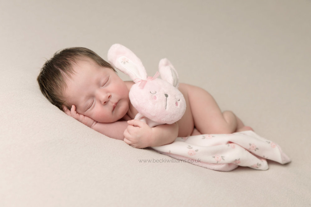 newborn baby girl hugs her bunny while sleeping during her newborn baby photo shoot in Hemel Hempstead