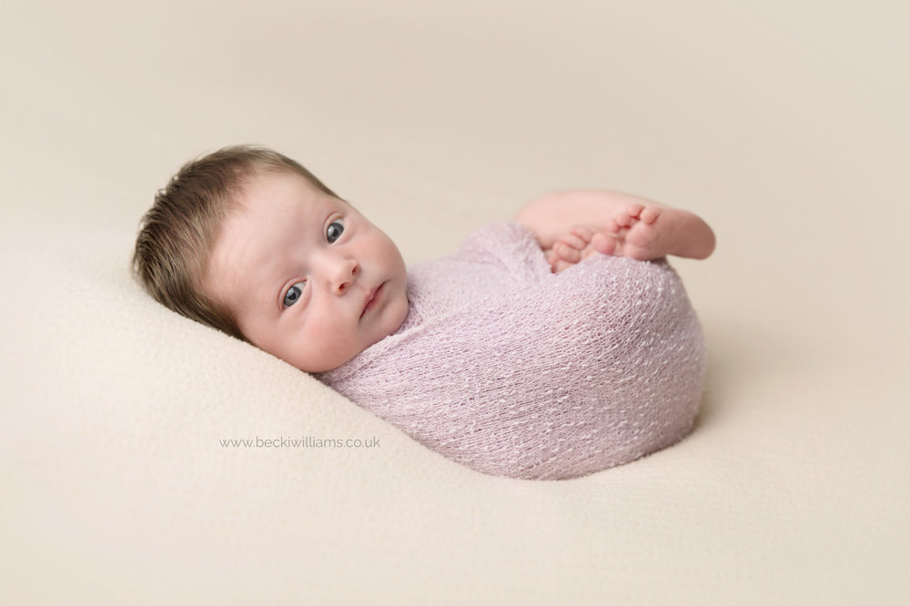 newborn baby girl is wrapped in a purple wrap with her eyes open during her newborn baby photo shoot in Hemel Hempstead