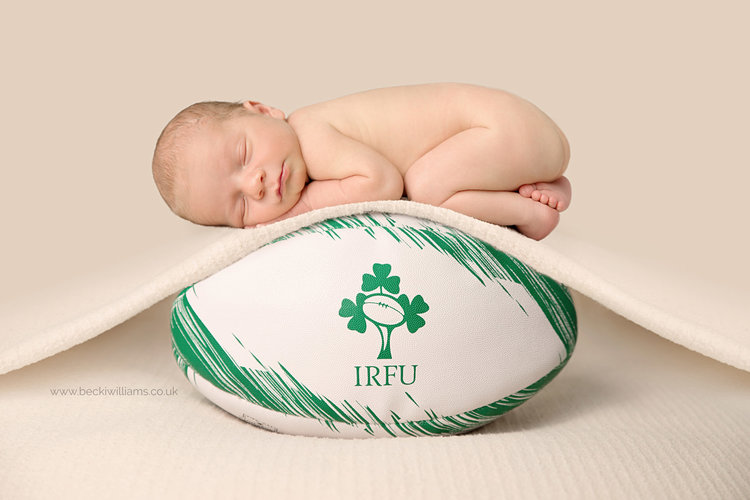 Newborn baby on rugby ball for newborn baby photoshoot in hemel hempstead with becki williams photography